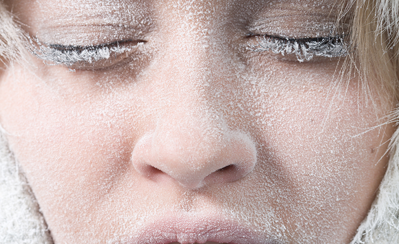 A closeup of a woman's frost covered face